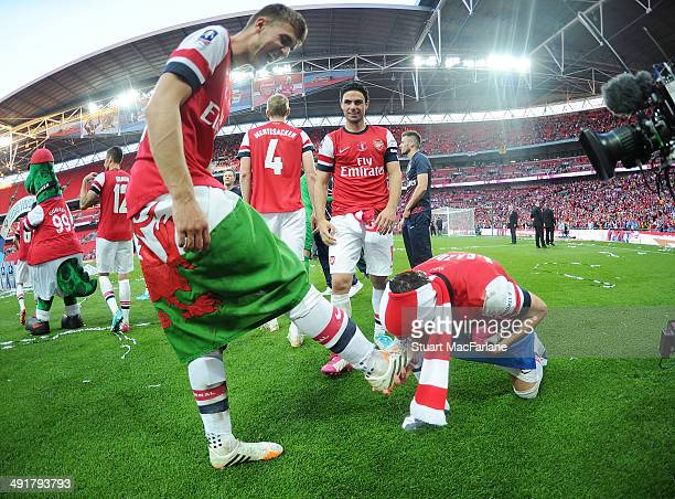 Arsenal's Aaorn Ramsey and Santi Cazorla celebrate after the FA Cup Final between Arsenal and Hull City at Wembley Stadium on May 17, 2014 in London,...