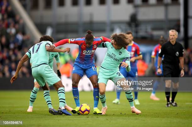 Arsenal's Alex Iwobi and Matteo Guendouzi battle for the ball with Crystal Palace's Wilfried Zaha during the Premier League match at Selhurst Park...