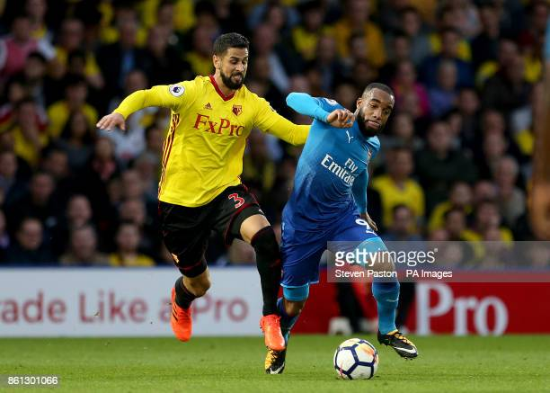 Arsenal's Alexandre Lacazette and Watford's Miguel Britos battle for the ball during the Premier League match at Vicarage Road Watford