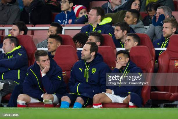 Arsenal's Alexis Sanchez and Aaron Ramsey look dejected on the bench with their head in their hands as they watch their side 15 down during the UEFA...
