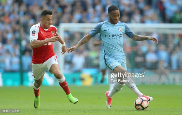 Arsenal's Alexis Sanchez and Manchester City's Raheem Sterling battle for the ball