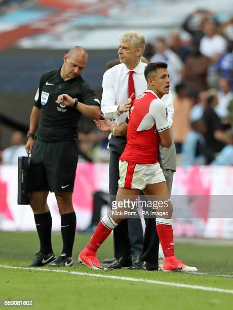 Arsenal's Alexis Sanchez gets a pat on the back from Arsenal manager Arsene Wenger after he leaves the pitch during the Emirates FA Cup Final at...