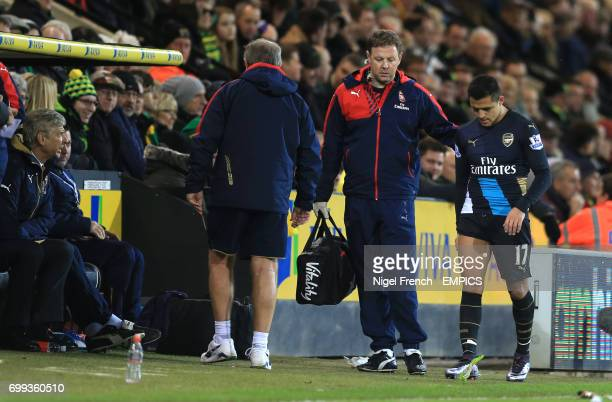 Arsenal's Alexis Sanchez leaves the field injured against Norwich City as his manager Arsene Wenger looks on