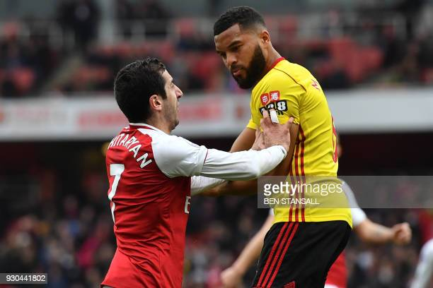 TOPSHOT Arsenal's Armenian midfielder Henrikh Mkhitaryan clashes with Watford's Englishborn Jamaican defender Adrian Mariappa during the English...