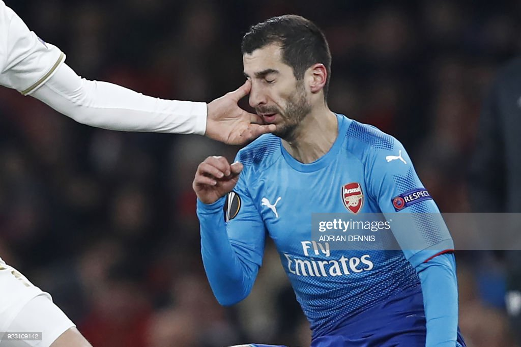 Arsenal's Armenian midfielder Henrikh Mkhitaryan gets a thumb in the eye from Ostersunds' English midfielder Jamie Hopcutt during the second leg of the Europa League Round of 32 football match between Arsenal and Ostersunds at the Emirates Stadium in London on February 22, 2018. / AFP PHOTO / Adrian DENNIS / RESTRICTED TO EDITORIAL USE. No use with unauthorized audio, video, data, fixture lists, club/league logos or 'live' services. Online in-match use limited to 75 images, no video emulation. No use in betting, games or single club/league/player publications. /