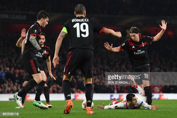 Arsenal's Armenian midfielder Henrikh Mkhitaryan goes down by AC Milan's Italian midfielder Riccardo Montolivo during the UEFA Europa League round of...