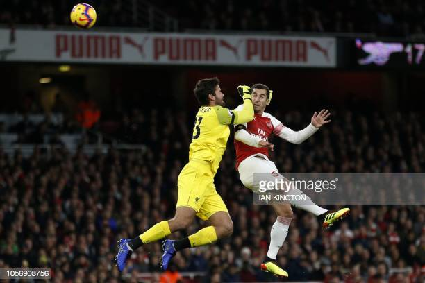 TOPSHOT Arsenal's Armenian midfielder Henrikh Mkhitaryan heads wide as Liverpool's Brazilian goalkeeper Alisson Becker comes out to challenge during...