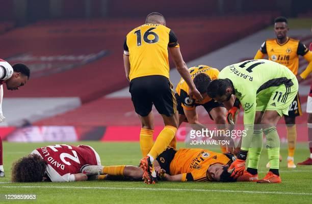 Arsenal's Brazilian defender David Luiz and Wolverhampton Wanderers' Mexican striker Raul Jimenez lay injured after clashing heads during the English...