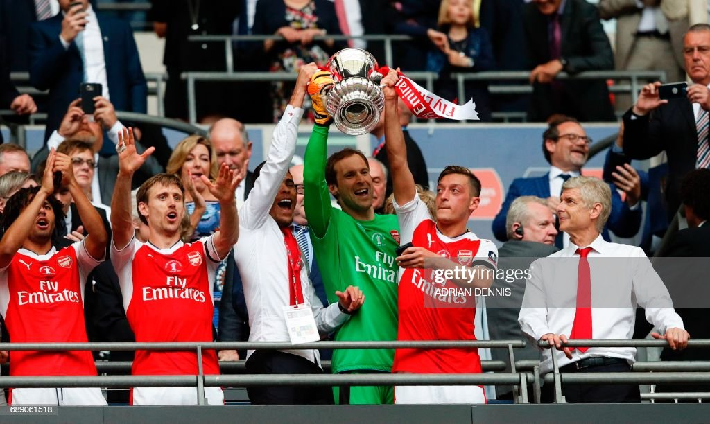 Arsenal's Brazilian defender Gabriel, Arsenal's Czech goalkeeper Petr Cech and Arsenal's German midfielder Mesut Ozil lift up the FA Cup trophy as Arsenal's French manager Arsene Wenger (R) looks on as Arsenal players celebrate their victory over Chelsea in the English FA Cup final football match between Arsenal and Chelsea at Wembley stadium in London on May 27, 2017. Aaron Ramsey scored a 79th-minute header to earn Arsenal a stunning 2-1 win over Double-chasing Chelsea on Saturday and deliver embattled manager Arsene Wenger a record seventh FA Cup. / AFP PHOTO / Adrian DENNIS / NOT