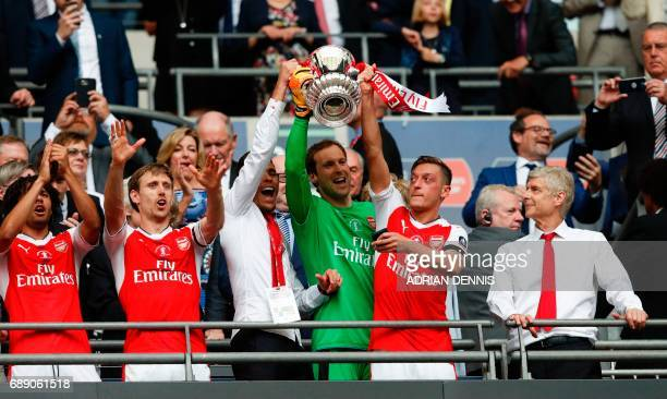 Arsenal's Brazilian defender Gabriel Arsenal's Czech goalkeeper Petr Cech and Arsenal's German midfielder Mesut Ozil lift up the FA Cup trophy as...