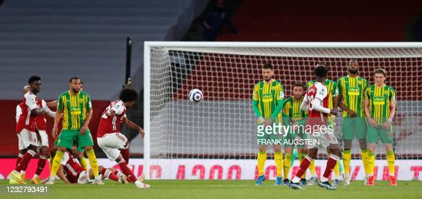 Arsenal's Brazilian midfielder Willian shoots to score his team's third goal from a free kick during the English Premier League football match...