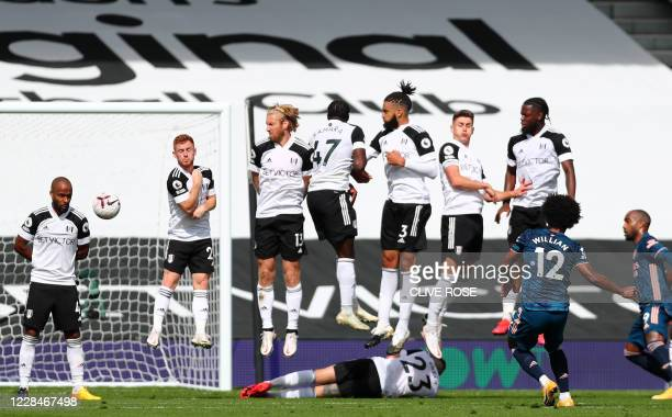 Arsenal's Brazilian midfielder Willian strikes a free kick that hits the post during the English Premier League football match between Fulham and...