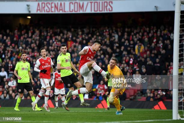Arsenal's Brazilian striker Gabriel Martinelli scores the opening goal past Sheffield United's English goalkeeper Dean Henderson during the English...
