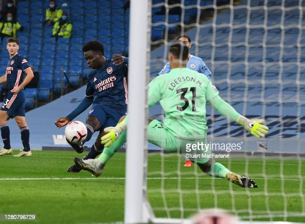 Arsenal's Bukayo Saka has his shot saved by Manchester City goalkeeper Ederson during the Premier League match between Manchester City and Arsenal at...