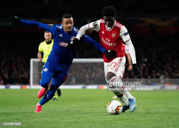 LONDON ENGLAND FEBRUARY Arsenal's Bukayo Saka is tackled by Olympiakos' Bruno Gaspar during the UEFA Europa League round of 32 second leg match...