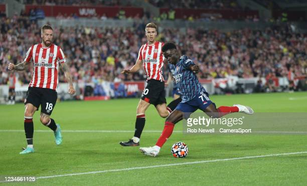 Arsenal's Bukayo Saka lines up a cross under pressure from Brentford's Kristoffer Ajer and Pontus Jansson during the Premier League match between...