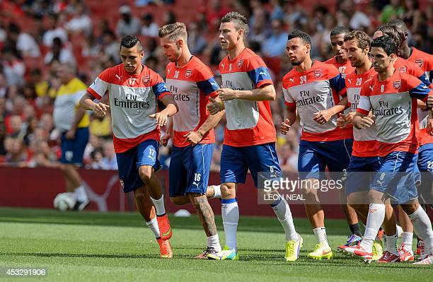 Arsenal's Chilean forward Alexis Sanchez almost collides with teammate Welsh midfielder Aaron Ramsey as they warm up during the first team training...