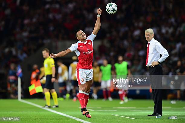 Arsenal's Chilean forward Alexis Sanchez reacts next to Arsenal's French manager Arsene Wenger during the UEFA Champions League Group A football...