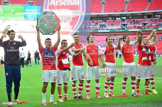 Arsenal's Chilean midfielder Alexis Sanchez raises the Community Shield trophy with teammates Arsenal's Spanish midfielder Santi Cazorla Arsenal's...