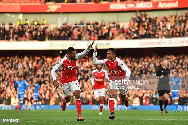 Arsenal's Chilean striker Alexis Sanchez celebrates with Arsenal's English midfielder Theo Walcott after scoring the opening goal of the English...