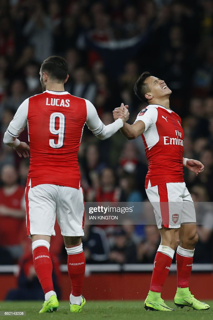 Arsenal's Chilean striker Alexis Sanchez (R) celebrates with Arsenal's Spanish striker Lucas Perez (L) after scoring their fourth goal during the English FA cup quarter final football match between Arsenal and Lincoln City at The Emirates Stadium in London on March 11, 2017. / AFP PHOTO / Ian KINGTON / RESTRICTED TO EDITORIAL USE. No use with unauthorized audio, video, data, fixture lists, club/league logos or 'live' services. Online in-match use limited to 75 images, no video emulation. No use in betting, games or single club/league/player publications. /