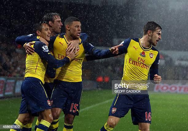 Arsenal's Chilean striker Alexis Sanchez celebrates with teammates Arsenal's Welsh midfielder Aaron Ramsey and Arsenal's English midfielder Alex...