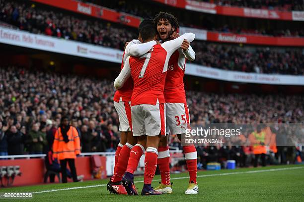 Arsenal's Chilean striker Alexis Sanchez celebrates with teammates after scoring the opening goal of the English Premier League football match...