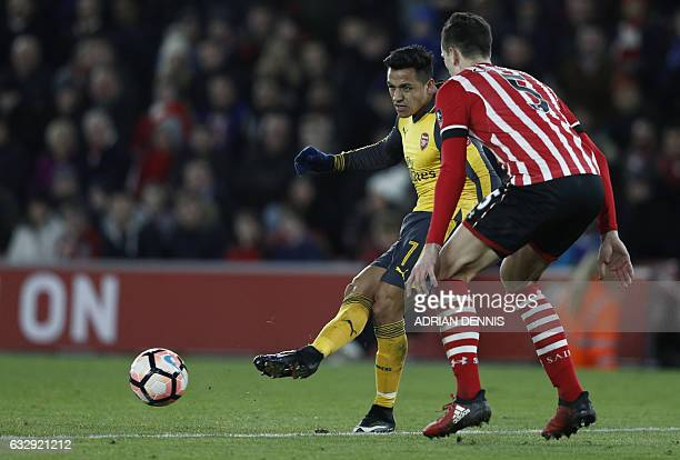 Arsenal's Chilean striker Alexis Sanchez corsses the ball to Arsenal's English midfielder Theo Walcott setting him up to score the team's fifth goal...