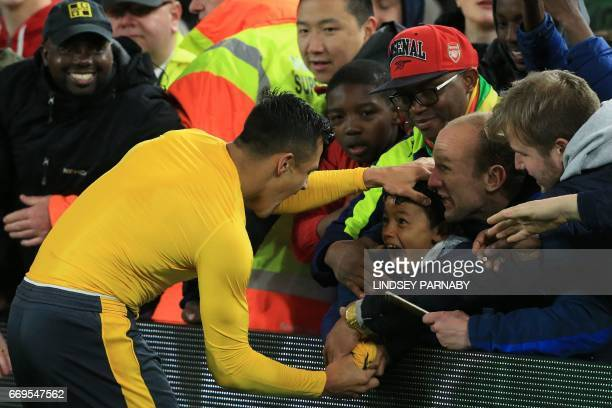 Arsenal's Chilean striker Alexis Sanchez gives his match shirt to a young fan following the English Premier League football match between...