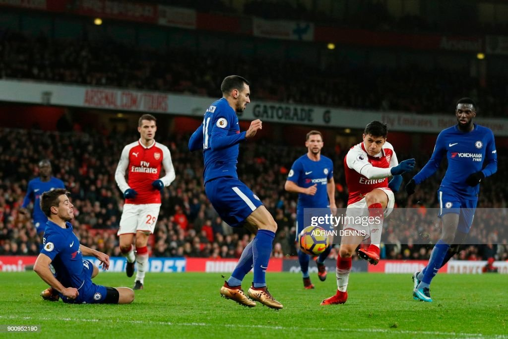 Arsenal's Chilean striker Alexis Sanchez (2R) has a shot on goal by Chelsea's Italian defender Davide Zappacosta during the English Premier League football match between Arsenal and Chelsea at the Emirates Stadium in London on January 3, 2018. / AFP PHOTO / Adrian DENNIS / RESTRICTED TO EDITORIAL USE. No use with unauthorized audio, video, data, fixture lists, club/league logos or 'live' services. Online in-match use limited to 75 images, no video emulation. No use in betting, games or single club/league/player publications. /