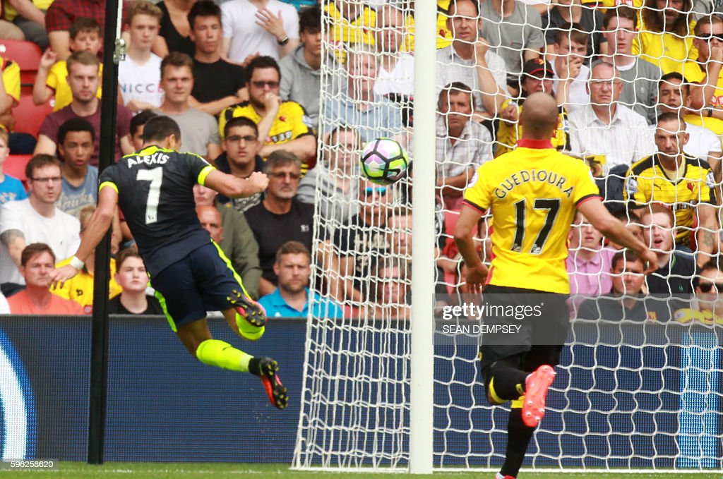 Arsenal's Chilean striker Alexis Sanchez (L) heads home their second goal during the English Premier League football match between Watford and Arsenal at Vicarage Road Stadium in Watford, north of London on August 27, 2016. Arsenal won the game 3-1. / AFP / Sean Dempsey / RESTRICTED TO EDITORIAL USE. No use with unauthorized audio, video, data, fixture lists, club/league logos or 'live' services. Online in-match use limited to 75 images, no video emulation. No use in betting, games or single club/league/player publications. /