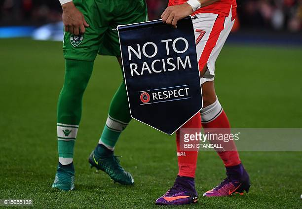 Arsenal's Chilean striker Alexis Sanchez holds an antiracism banner ahead of the UEFA Champions League Group A football match between Arsenal and...