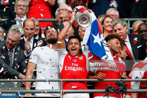 Arsenal's Chilean striker Alexis Sanchez lifts the FA Cup trophy as Arsenal players celebrate their victory over Chelsea in the English FA Cup final...