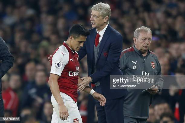Arsenal's Chilean striker Alexis Sanchez passes Arsenal's French manager Arsene Wenger as he substituted off of the pitch during the English Premier...