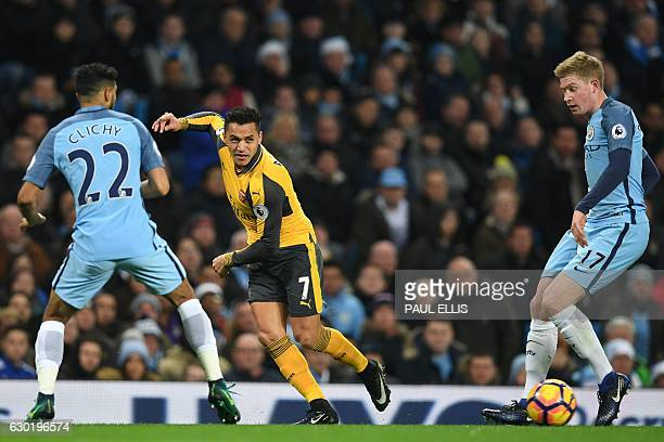 Arsenal's Chilean striker Alexis Sanchez passes the ball between Manchester City's French defender Gael Clichy and Manchester City's Belgian...
