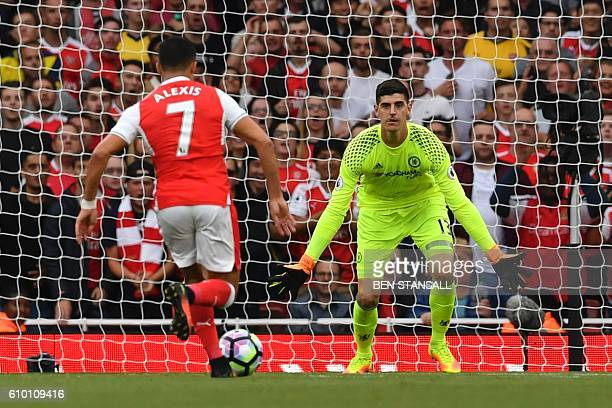 Arsenal's Chilean striker Alexis Sanchez runs in to score the opening goal past Chelsea's Belgian goalkeeper Thibaut Courtois during the English...