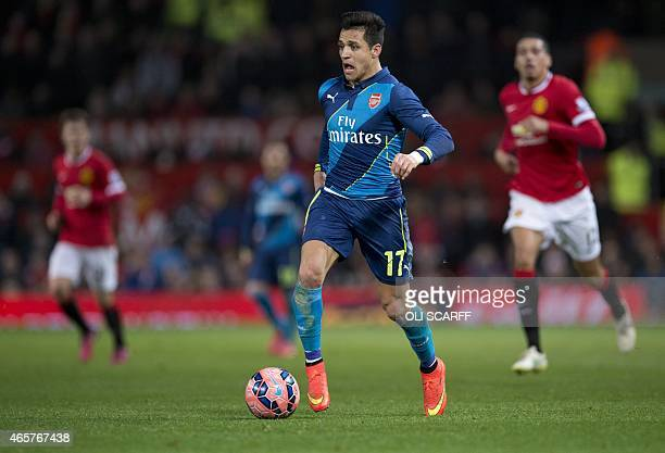 Arsenal's Chilean striker Alexis Sanchez runs with the ball during the FA Cup quarterfinal football match between Manchester United and Arsenal at...