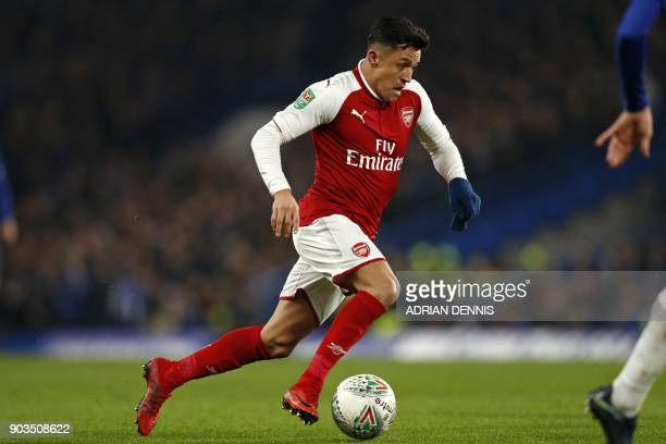 Arsenal's Chilean striker Alexis Sanchez runs with the ball during the English League Cup semifinal first leg football match between Chelsea and...