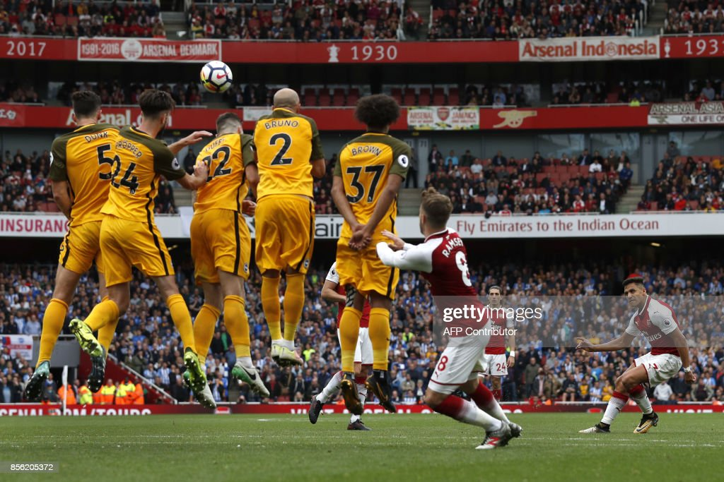 TOPSHOT - Arsenal's Chilean striker Alexis Sanchez (R) takes a free kick at goal during the English Premier League football match between Arsenal and Brighton at the Emirates Stadium in London on October 1, 2017. / AFP PHOTO / Adrian DENNIS / RESTRICTED TO EDITORIAL USE. No use with unauthorized audio, video, data, fixture lists, club/league logos or 'live' services. Online in-match use limited to 75 images, no video emulation. No use in betting, games or single club/league/player publications. /