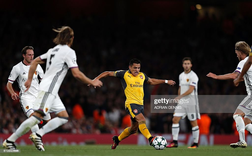 TOPSHOT - Arsenal's Chilean striker Alexis Sanchez (C) takes on the Basel defence during the UEFA Champions League Group A football match between Arsenal and FC Basel at The Emirates Stadium in London on September 28, 2016. / AFP / Adrian DENNIS