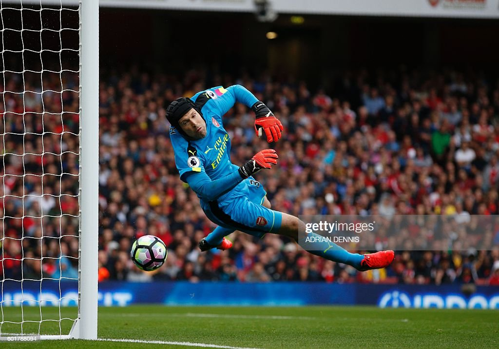 TOPSHOT - Arsenal's Czech goalkeeper Petr Cech cannot prevent the ball rebounding off his back, into the net after hitting the bar following a freekick from Southampton's Serbian midfielder Dusan Tadic (not pictured) during the English Premier League football match between Arsenal and Southampton at the Emirates Stadium in London on September 10, 2016. / AFP / Adrian DENNIS / RESTRICTED TO EDITORIAL USE. No use with unauthorized audio, video, data, fixture lists, club/league logos or 'live' services. Online in-match use limited to 75 images, no video emulation. No use in betting, games or single club/league/player publications. /