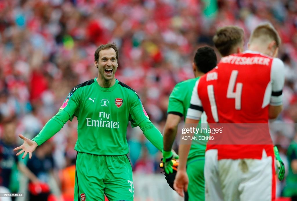 Arsenal's Czech goalkeeper Petr Cech (L) celebrates with his teammates on the pitch after the English FA Cup final football match between Arsenal and Chelsea at Wembley stadium in London on May 27, 2017. Arsenal won the game 2-1. / AFP PHOTO / Adrian DENNIS / NOT