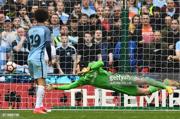 Arsenal's Czech goalkeeper Petr Cech dives to prevent a goal during the FA Cup semifinal football match between Arsenal and Manchester City at...