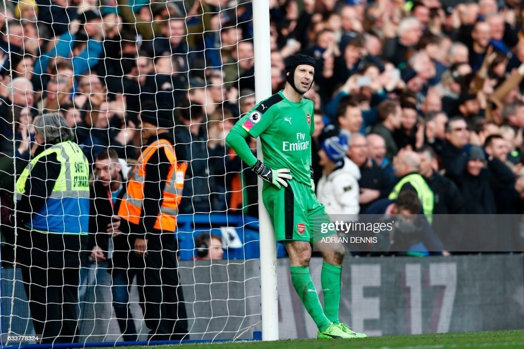 Arsenal's Czech goalkeeper Petr Cech reacts after Chelsea's Spanish midfielder Cesc Fabregas scored their third goal during the English Premier League football match between Chelsea and Arsenal at Stamford Bridge in London on February 4, 2017. / AFP PHOTO / Adrian DENNIS / RESTRICTED TO EDITORIAL USE. No use with unauthorized audio, video, data, fixture lists, club/league logos or 'live' services. Online in-match use limited to 75 images, no video emulation. No use in betting, games or single club/league/player publications. /