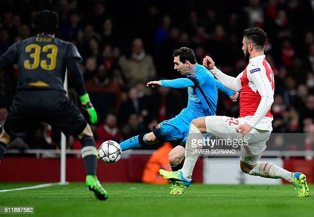 Arsenal's Czech goalkeeper Petr Cech watches Arsenal's French striker Olivier Giroud block a shot from Barcelona's Argentinian forward Lionel Messi...