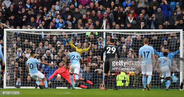 Arsenal's Czech goalkeeper Petr Cech watches as Manchester City's Argentinian striker Sergio Aguero shoots from the penalty spot to score his team's...