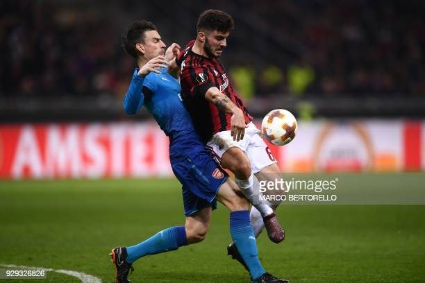 Arsenal's defender Laurent Koscielny of France fights for the ball with AC Milan's forward Patrick Cutrone from Italy during the UEFA Europa League...