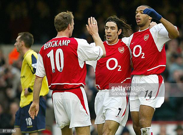 Arsenal's Dennis Bergkamp celebrates his goal Arsenal's second against Bolton with fellow goal scorer Robert Pires and Thierry Henry as Bolton's...