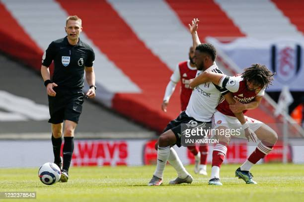 Arsenal's Egyptian midfielder Mohamed Elneny tangles with Fulham's English striker Ademola Lookman under the eye of referee Craig Pawson during the...