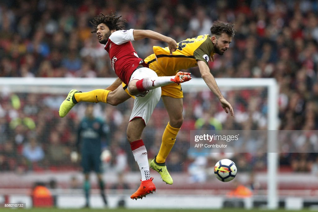 TOPSHOT - Arsenal's Egyptian midfielder Mohamed Elneny (L) vies with Brighton's Dutch midfielder Davy Propper during the English Premier League football match between Arsenal and Brighton at the Emirates Stadium in London on October 1, 2017. / AFP PHOTO / Adrian DENNIS / RESTRICTED TO EDITORIAL USE. No use with unauthorized audio, video, data, fixture lists, club/league logos or 'live' services. Online in-match use limited to 75 images, no video emulation. No use in betting, games or single club/league/player publications. /